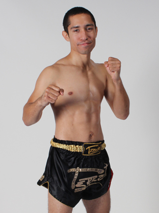Fighter wearing shorts and posing with fists up to chest height.