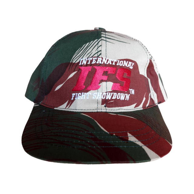 Camouflage baseball cap with tropical design and red and white IFS logo.